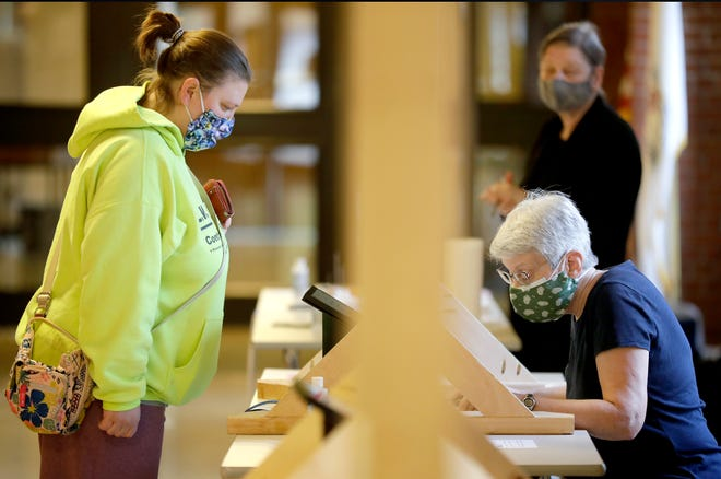 Tracy Buck of Appleton checks in with election inspector Linda Sheffler before casting her ballot at the polls located at First Congregational United Church of Christ on Tuesday in Appleton.