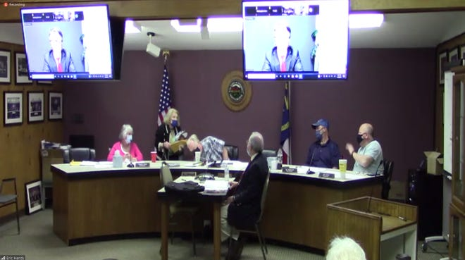 Barbara Lamb, Woodfin Planning and Zoning Board of Adjustment member, leaves the dais after recusing herself at the board's April 5 meeting. The board was left without a quorum after her recusal. It's an issue the town still hasn't solved, voting again May 3 to move the meeting back another month.