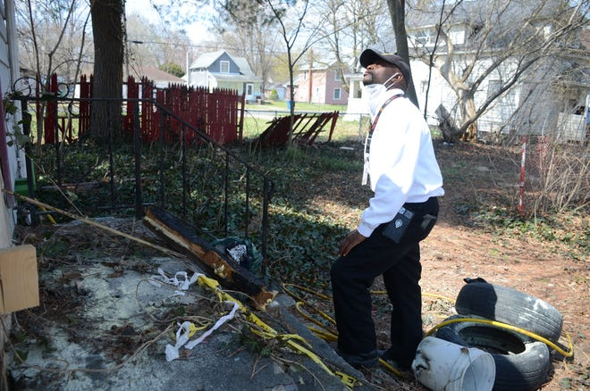 Fire Marshal Quincy Jones looks over damage to 203 Post Ave. from a fire set early Saturday.