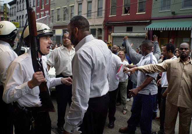 Cincinnati Police confront members of the New Prospect Baptist Church on Elm Street and 18th Street as they walk down Elder Ave. in Findlay market in April 2001. Protestors rioted throughout the day after the shooting death of Timothy Thomas in Over-the-Rhine.
