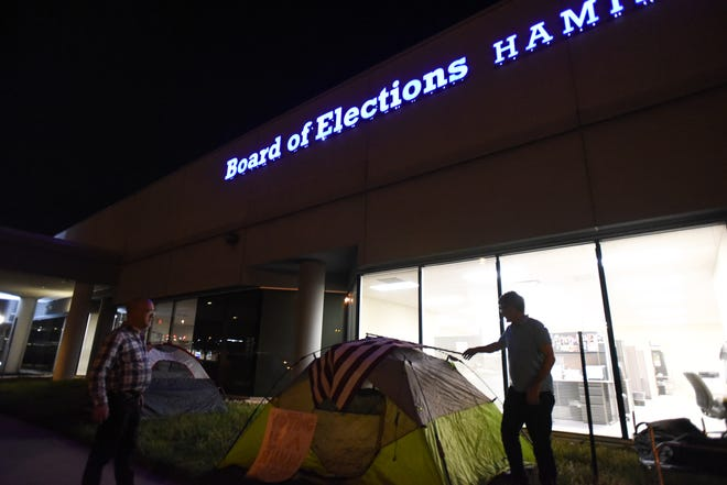 Brian Garry (right) and Lew Ebstein set up tents to camp outside of the Hamilton County Board of Elections overnight to promote early voting month.