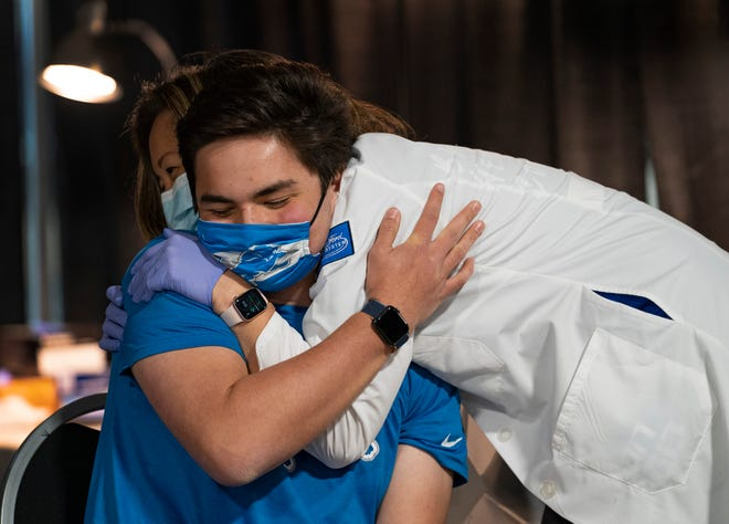 Associate Chief Clinical Officer/Chief Quality Officer, Henry Ford Health System Dr. Betty Chu hugs her 16-year-old son Aidan Shoresh after giving him his Covid vaccine on Tuesday, Apr. 6, 2021 at Ford Field.