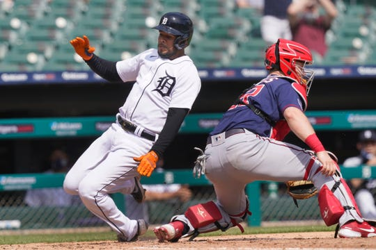 The Detroit Tigers 'Jeimer Candelario strikes the throw to Minnesota Twins catcher Ryan Jeffers to score from first on teammate Robbie Grossmans' double in the fourth inning of a baseball game, Tuesday, April 6, 2021, in Detroit.