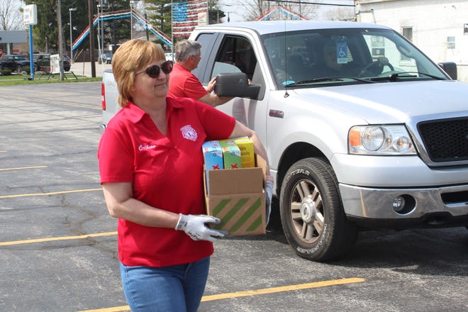Colleen Carmack of the Fremont Lions Club carries a box of food donations Tuesday at the Fremont Eagles 712 parking lot on W. State Street. The Lions and Fremont Kiwanis have been collecting non- perishable items for the Sandusky County Food Pantry and Pontifex.