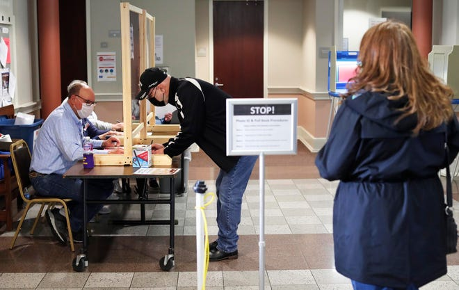Mike Freeman, of Two Rivers, has his id checked before voting at the Two Rivers City Hall, Tuesday, April 6, 2021, in Two Rivers, Wis. At right is his wife Kim waiting for her turn.