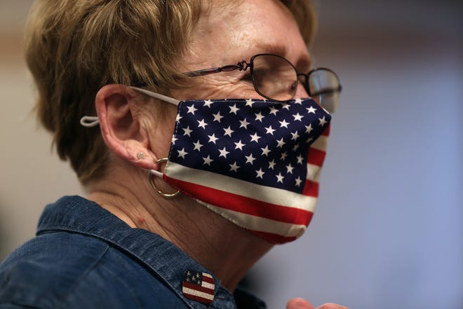 Thiensville election chief inspector Mary R. Giuliani sports an American flag mask and pin on election day at Thiensville Village Hall on Tuesday, April 6, 2021.