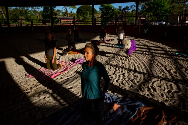 Cindy Kuhl, the office administrator and data base coordinator at Naples Therapeutic Riding Center participates in a miniature horse yoga class on Monday, April 5, 2021, in North Naples.
