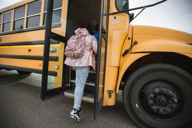 Cheriche Sanders gets on the school bus at the bus stop waiting for the bus on the first in-person school day in Las Cruces on Tuesday, April 6, 2021.