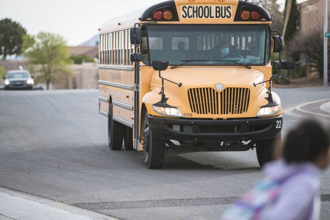 Parents and children wait at the bus stop on the first in-person school day in Las Cruces on Tuesday, April 6, 2021.