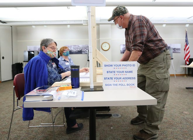 Lin Schrottky gets Andrew Sonnleitner's information in the spring elections Tuesday at the Oshkosh Public Library.