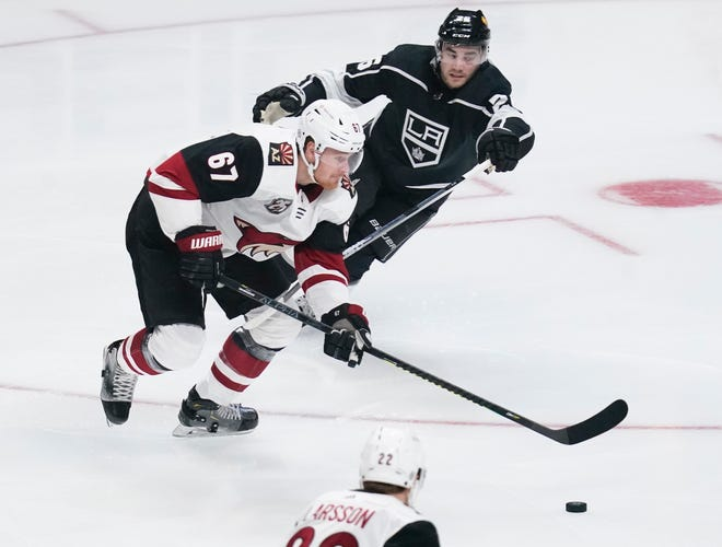 Apr 5, 2021; Los Angeles, California, USA; Arizona Coyotes left wing Lawson Crouse (67) moves the puck down the ice past Los Angeles Kings defenseman Sean Walker (26) during the first period at Staples Center. Mandatory Credit: Robert Hanashiro-USA TODAY Sports