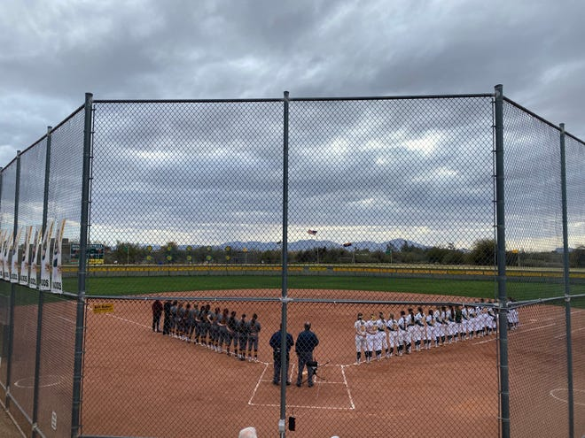 Canyon del Oro and Nogales softball teams stand during the National Anthem before their game on March 26 in Oro Valley, Ariz.