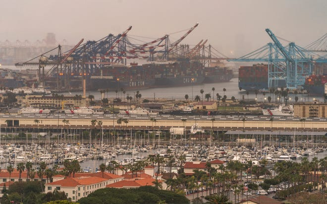 In this Wednesday, March 3, 2021 photo, container cargo ships are seen docked in the Port of Los Angeles.  A trade bottleneck born of the COVID-19 outbreak has U.S. businesses waiting for shipments from Asia _ while off the coast of California, dozens of container ships have been anchored, unable to unload their cargo.