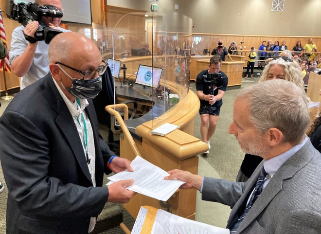 Tim Saunders of Redding hands Shasta County Supervisor Joe Chimenti a notice of intent to recall him from office Tuesday, April 6, 2021, at the supervisors meeting. The other two supervisors in the recall effort are Leonard Moty and Mary Rickert.