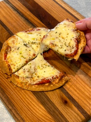 The tortilla pizza starts in a cast iron skillet to provide a jump start on the crispinessof the crust.