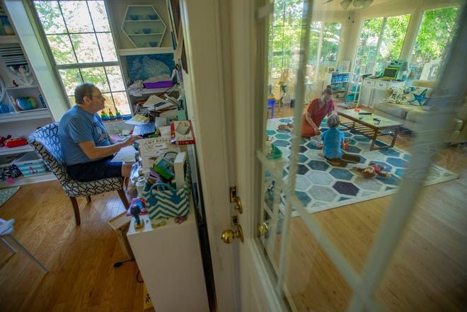 Jonathan Grant, a professor at Florida State University, left, reads a student's paper while his son Camden, 6, works with his tutor in the next room Tuesday, April 6, 2021.