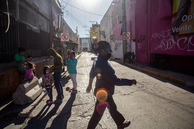 Marie Martine walks in downtown Cuidad Juarez past Central American migrants near the Paso Norte Bridge.