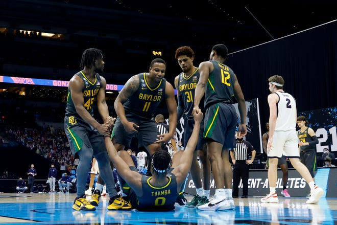 Flo Thamba of the Baylor Bears is helped up off the court by teammates in the National Championship game of the 2021 NCAA Men's Basketball Tournament at Lucas Oil Stadium.