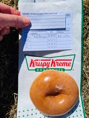 Debbie Nelson, a Denver resident, celebrates getting her first COVID-19 vaccine by showing her vaccination card at Krispy Kreme to receive a free donut.