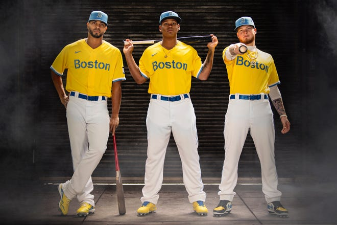 April 6, 2021, Boston, MA: Boston Red Sox shortstop Xander Bogaerts, third baseman Rafael Devers, and outfielder Alex Verdugo pose for a portrait as they display 2021 Boston Red Sox Nike City Connect uniform at Fenway Park in Boston, Massachusetts Tuesday, April 6, 2021.   (Photo by Billie Weiss/Boston Red Sox/Nike)