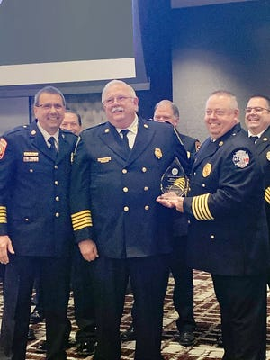 Travis County ESD No. 2 Chief Ron Moellenberg (center) receives the Lone Star Achievement Award from Texas Fire Chiefs Association. Association President Les Stephens (right) and First Vice President Donnie Norman (left) present Moellenberg with the award on April 6 at the group's annual conference in College Station.