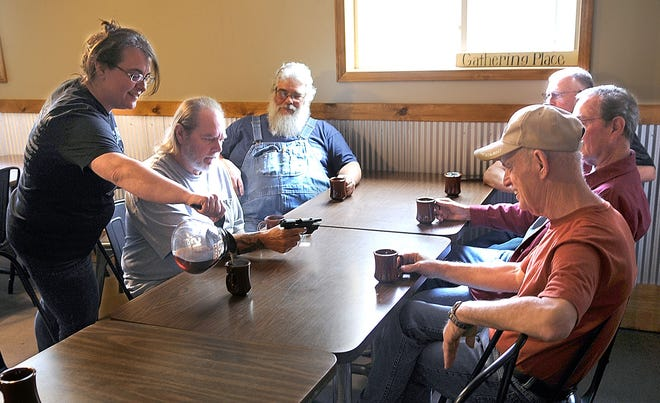 Cattlemans owner Mandy Close on Wednesday tops off the coffee cups for the members of the Guns & Coffee group (from left) Mike McCormick, Dave Rhine, James Dupee, Zane Cellar and Bill Porter who regularly meet at the Savannah restaurant.