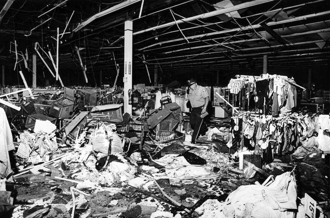 A police officer sifts through debris on June 1, 1985 at the Jamesway department store in the Big Beaver Plaza shopping center.