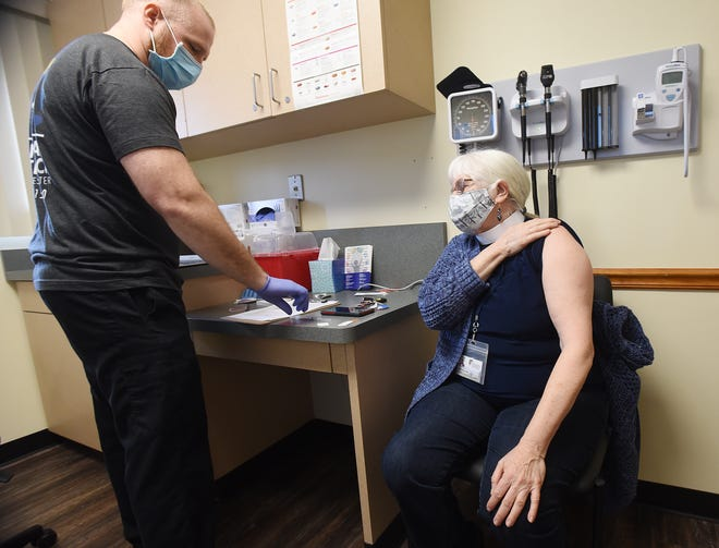 Nurse practitioner Alex Tatangelo counsels Linda Schlafer, of Monaca, before giving her the Pfizer COVID-19 vaccine Wednesday at Central Outreach Wellness Center in Aliquippa.