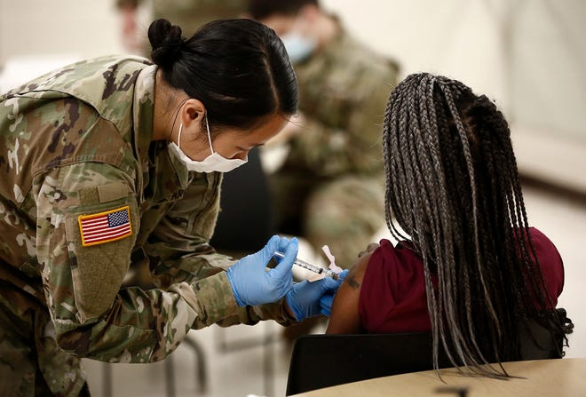 Ohio National Guard Spc. Angie Chen gives a COVID-19 vaccine to a woman at PrimaryOne Health in April. The FDA could grant approval for a third Pfizer COVID vaccine as early as Friday, with the White House planning to begin boosters on Sept. 20.