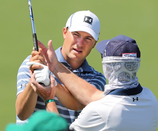 Jordan Spieth, who on Sunday won a tournament for the first time since 2017,  works with his swing doctor, Cameron McCormick, on practice range at Augusta National Golf Club on Monday.