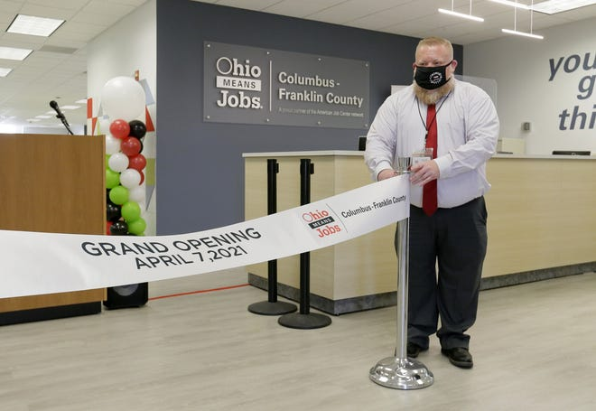 Scott Johnson hangs a ceremonial ribbon inside the newly renovated OhioMeansJobs center before a grand opening event Wednesday.