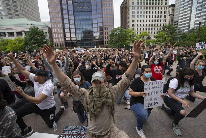 Demonstrators take a knee and hold their hands in the air outside the Ohio Statehouse during a peaceful protest for George Floyd in downtown Columbus on Monday, June 1, 2020. Four bills pending in the Ohio Legislature would add new penalties and increase others for offenses at protests.
