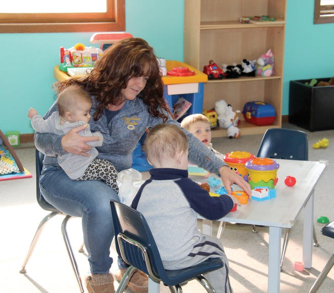 """Janelle Berhow is pictured this week with some of the children in her care at her child care business, """"Gotta Love Kids"""" that she and her husband, Mark Berhow, opened earlier this year in downtown Crookston, in the former longtime location of New Paths Area Learning Center in the northwest corner of Downtown Square. Although because of Crookston's continued child care shortage many assumed the new child care operation would have a full roster of kids from day one, Janelle says she won't be full until May. The greatest need for licensed child care slots inCrookston is for infants, she adds."""