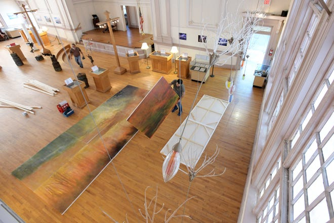 Franklin Matthews flips over the individual canvases that make up his 12-by-18-foot painting to assemble them together to be displayed on the stage of the Karpeles Manuscript Library Museum as part of the Th3Rivers Project show. Brett Waller worked with other artists to install the artwork for his upcoming group show that opens Friday and runs through May. The show involves the work of six different Northeast Florida artists whose work relates to the St. Johns River.