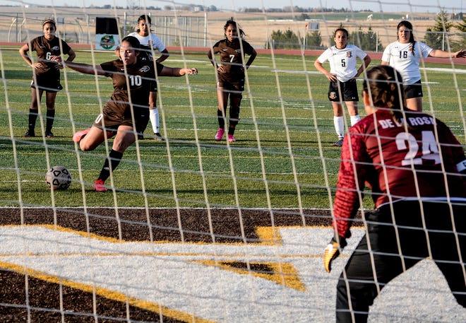 Garden City High School's Destiny Rojo sends a penalty kick past Guymon, Okla., goal keeper Naomi De La Rosa for a goal in the closing minutes of the first half Tuesday at Buffalo Stadium.