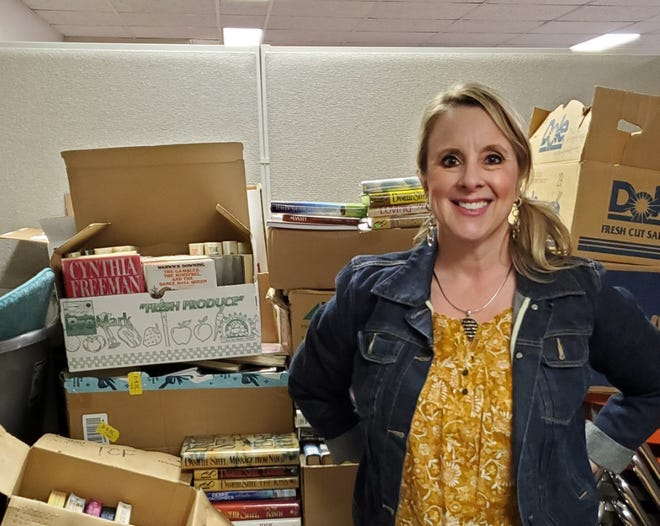 Dr. Sarah Broman Miller stands in a storage room at Hays First United Methodist Church with book donations for her to distribute to prisons in the state.