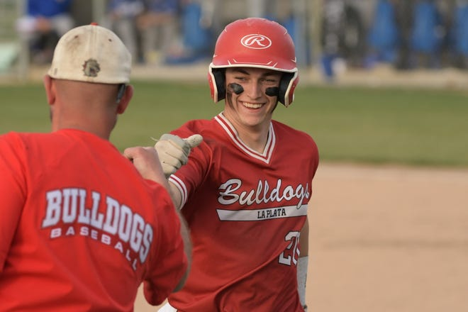 La Plata catcher Riley Case gives coach Josh Woodward a fist bump after coming off the bases for a pinch-runner.