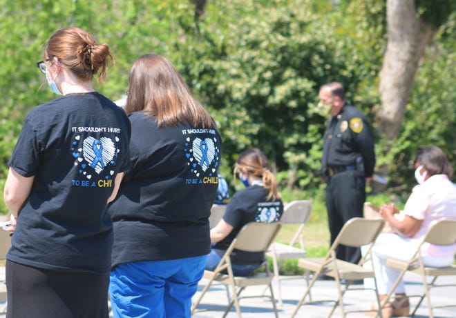 """Some people wore shirts that read """"It shouldn't hurt to be a child"""" Wednesday, April 7, at Pearson Park to kick off Child Abuse Prevention Month."""