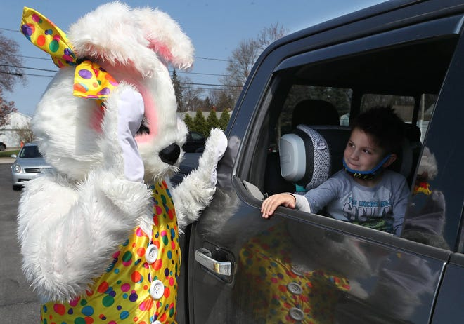 The Easter Bunny greets Will Voll, 4 at a drive-thru Easter event at Northfield Village Hall Gazebo on April 3. Volunteers gave out 150 bags of candy and gifts to families.