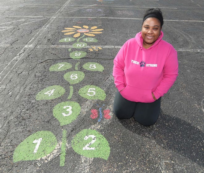 Rhonda Crawford, the president of the Bissell Elementary School PTA, kneels next to the start of one of the sensory walks in the parking lot of Twinsburg High School that Crawford and Bissell PTA volunteer coordinator Lisa Oddo made possible.