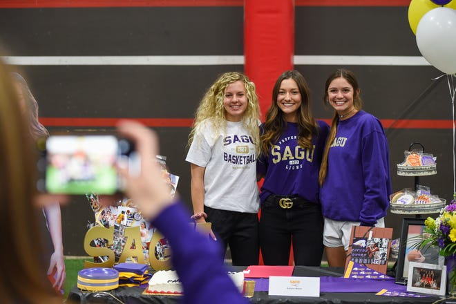 Lubbock-Cooper's Autumn Moore (center) takes a photo with Abernathy's Chanie Chambers (left) and Slaton's Mary Jo Parker after signing her national letter of intent to play basketball at Southwestern Assemblies of God University on Wednesday at Lubbock-Cooper High School in Woodrow, Texas. All three signed to become Lady Lions.