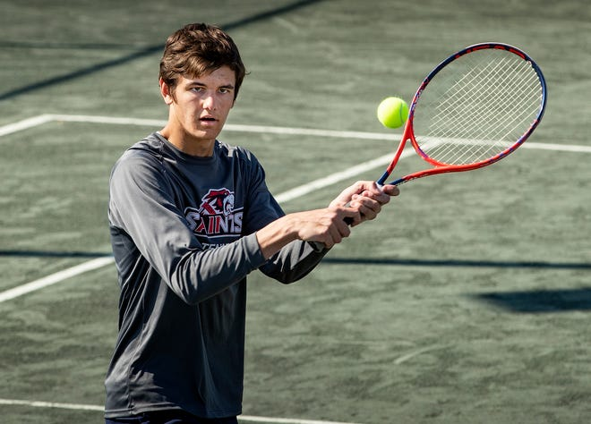 All Saints Jacob Bruschayt  returns serve during a doubles match during the East County Tennis Tournament Winter Haven City Courts in Winter Haven Fl. Monday April 5 2021. 