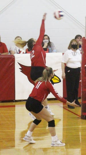 McClave High School's McKayla Kiniston (12) hits the ball over the net in Tuesday's match, while her sister, McKenzie, stands by. The Cardinals lost the match in three sets.