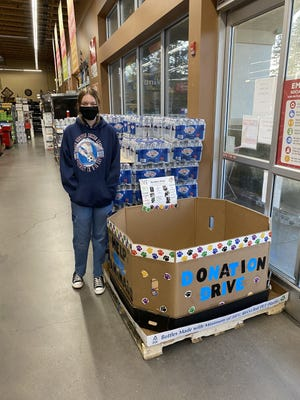 Mount Shasta Girl Scout Jessa Walker stands next to one of the donation boxes she created for a donation drive to benefit the Siskiyou Humane Society. This box is at Grocery Outlet in Weed; there are several boxes available in the Mt. Shasta area.