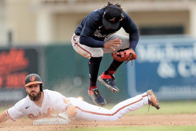 The Baltimore Orioles' Ryan McKenna (65) steals second base as Atlanta Braves second baseman Ozzie Albies (1) avoids him in the fifth inning of a spring training baseball game in 2020. McKenna made his major league regular-season debut Monday, April 5, 2021 at Yankee Stadium.