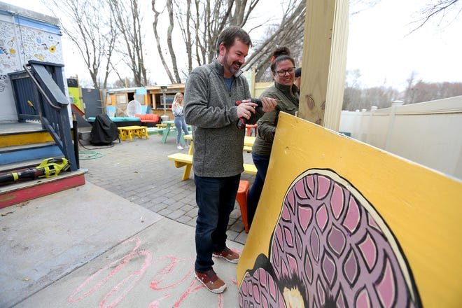 Owner Shane Pine and Heather Madison work to hang murals onto the wall of The Backyard  Wednesday, April 7, 2021, in Hampton.