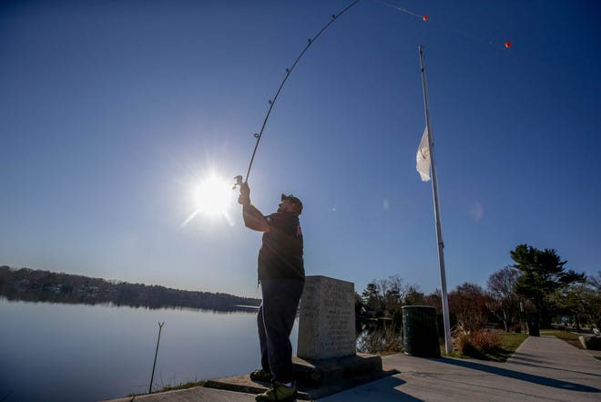 Rob Anika of Coventry enjoys the early opening of trout-fishing season at Tiogue Lake on Wednesday morning.