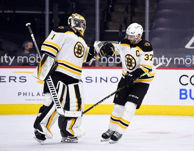 Boston Bruins' Patrice Bergeron, right, high-fives Jeremy Swayman after Bergeron scored a goal during the first period of an NHL hockey game against the Philadelphia Flyers, Tuesday, April 6, 2021, in Philadelphia. (AP Photo/Derik Hamilton)