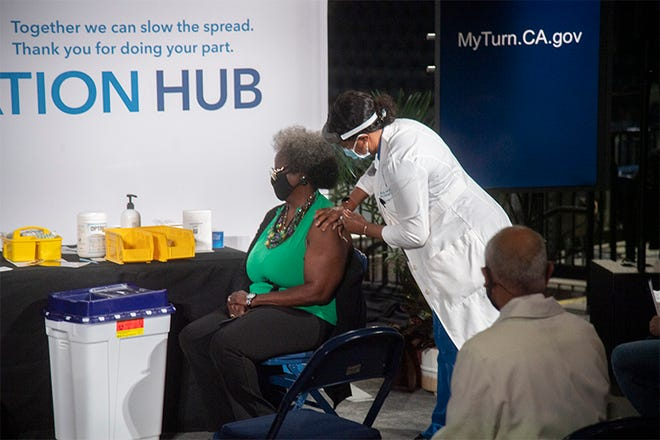 Arnetta Lee-Gray receives a COVID-19 vaccination during a media event at Stockton Arena before the Wednesday opening of the site as a vaccination hub.