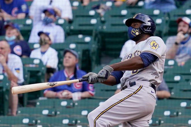 Milwaukee Brewers' Lorenzo Cain watches after hitting a three-run home run against the Chicago Cubs during the 10th inning in Chicago, Wednesday, April 7, 2021.